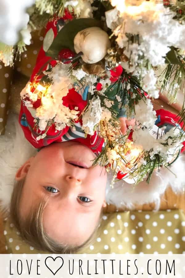 Baby peeking out from under the Christmas tree.