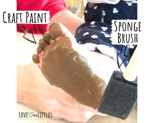 A photo of a baby foot with brown craft paint