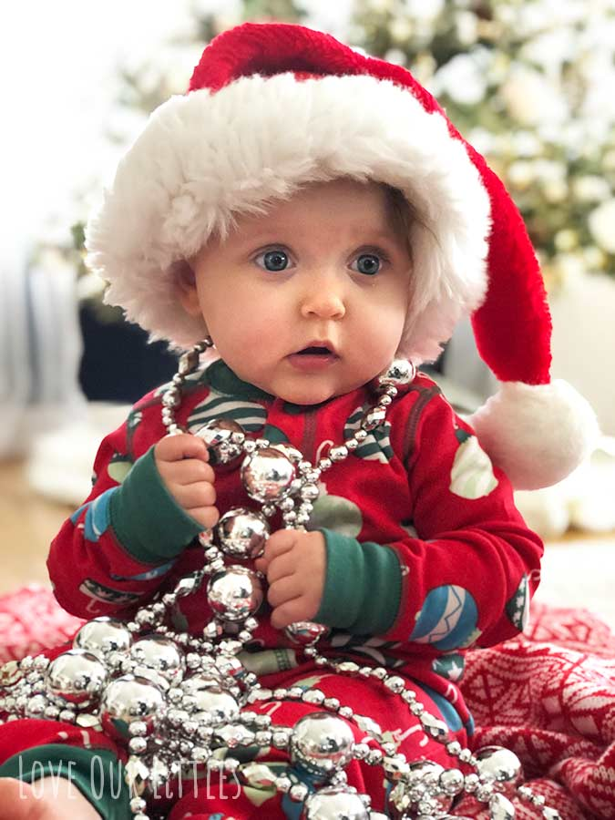 A picture of a baby wearing a Santa hat and christmas beads sitting in front of a christmas tree.
