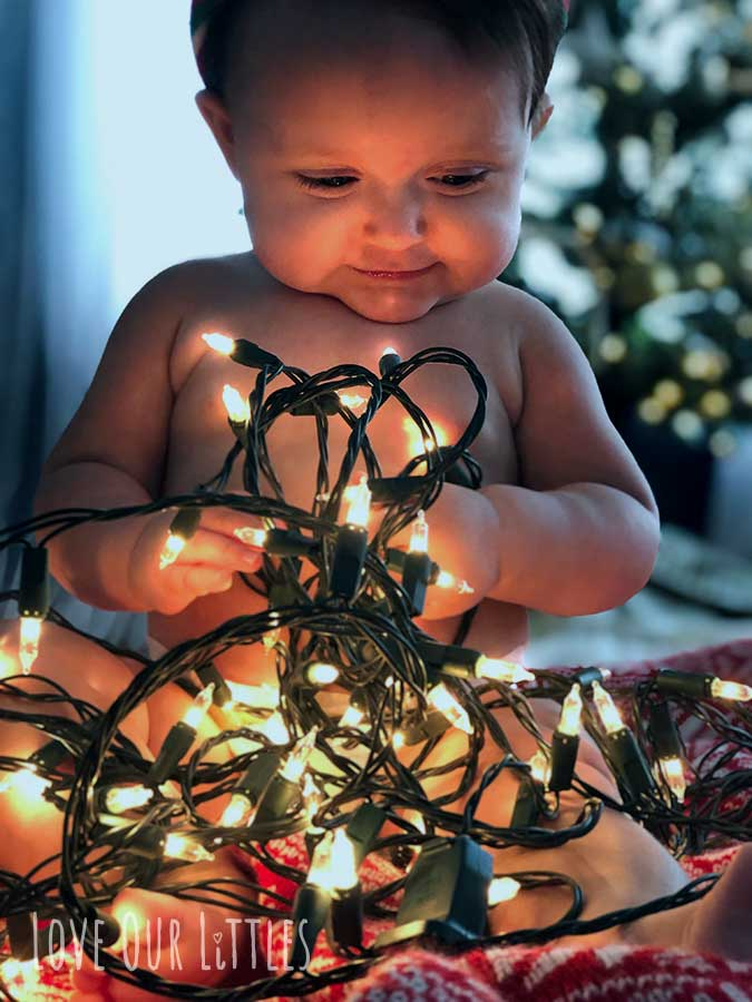 Picture of baby holding a string of lit up Christmas lights.