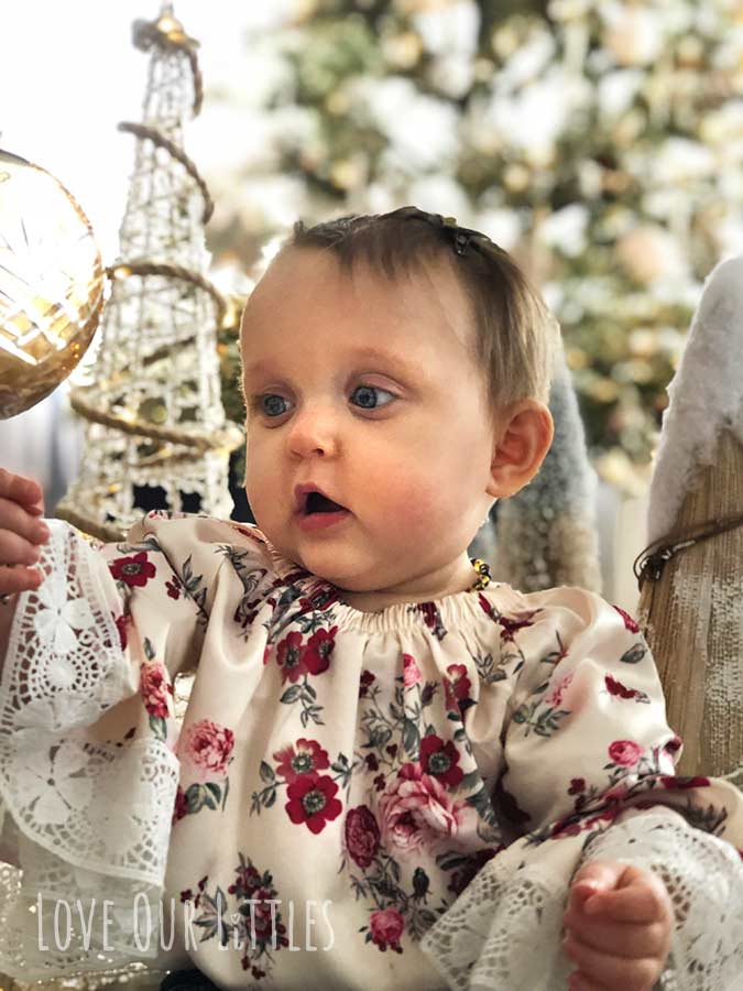 Christmas picture of a baby reaching out for a glass Christmas ornament with Christmas tree decor around her.