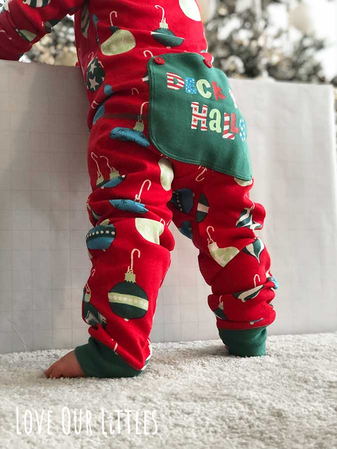 Christmas picture of baby's torso standing in a Christmas outfit.