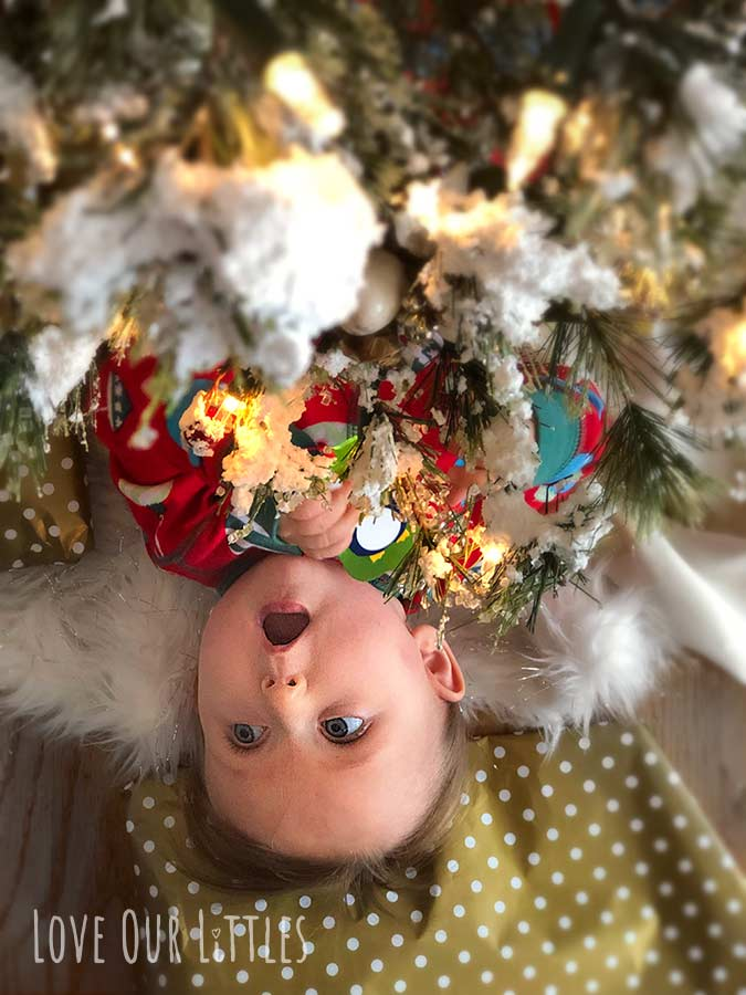 "Baby peeking out from under a Christmas tree with cute ""open-mouth"" expression."