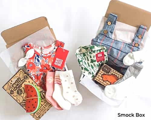 A photo of two open subscription boxes with baby clothes and accessories.