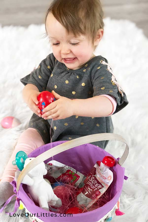 Baby playing with Easter eggs out of her first Easter basket.