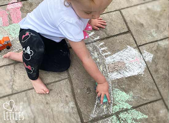 Toddler playing with chalk art roadway and town with a toy car.