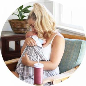 Mom sitting in a chair holding her newborn baby drinking a lactation smoothie with Milk Dust.