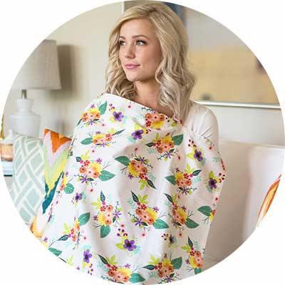 Mom breastfeeding infant under a floral pattern nursing cover.