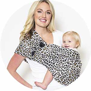 woman holding baby in a leopard print baby sling.