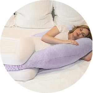 pregnant woman lying on the bed with her purple minky pregnancy pillow.