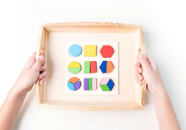 photo of cropped arms holding a tray of Montessori toy puzzles.