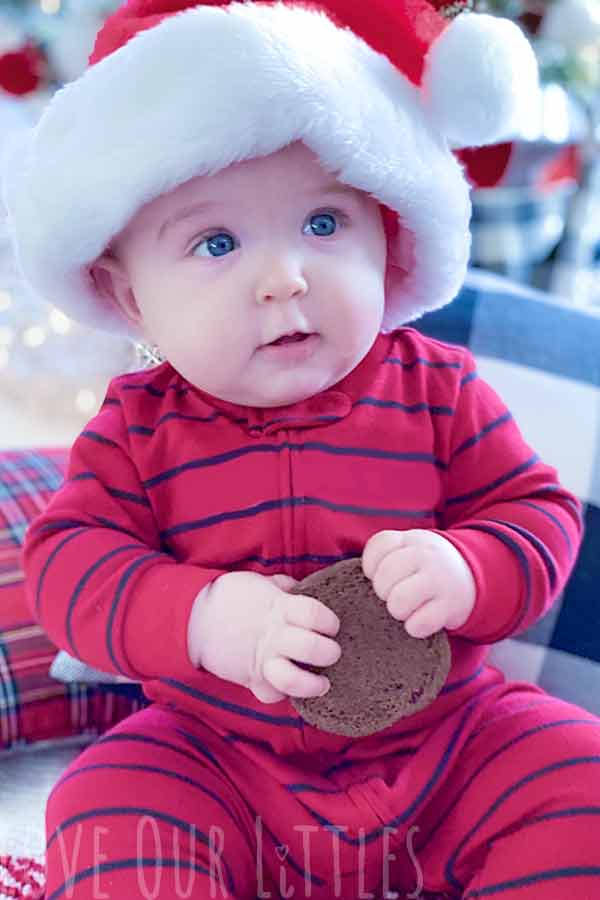Baby in a Christmas themed photo holding a chocolate cookie while wearing a red Santa hat.