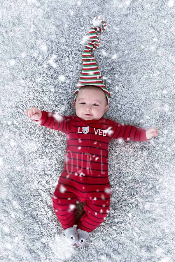 Christmas picture idea of baby lying on back on a white rug with digital snowflakes added on top.