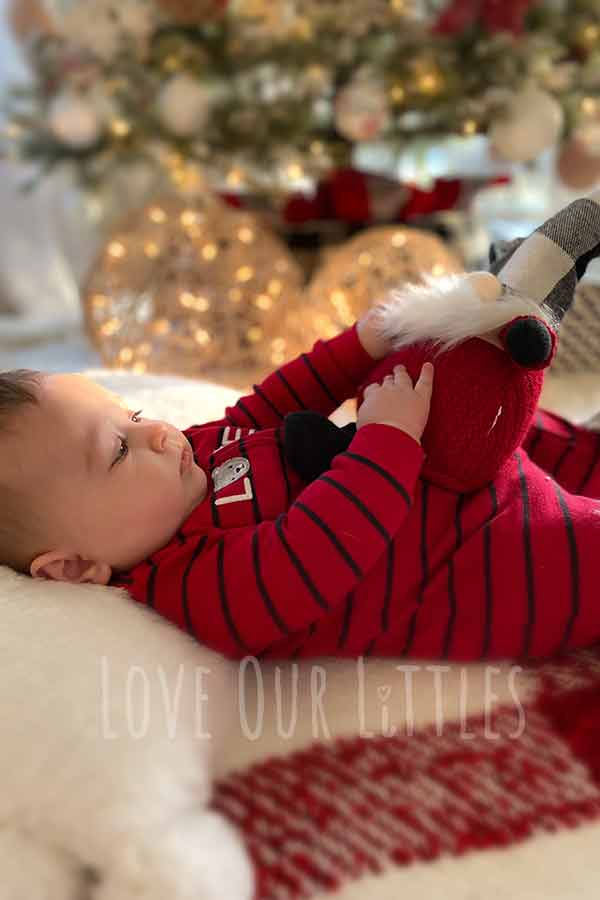 Christmas picture of a baby boy lying on his back holding a stuffed Christmas nome on his stomach.