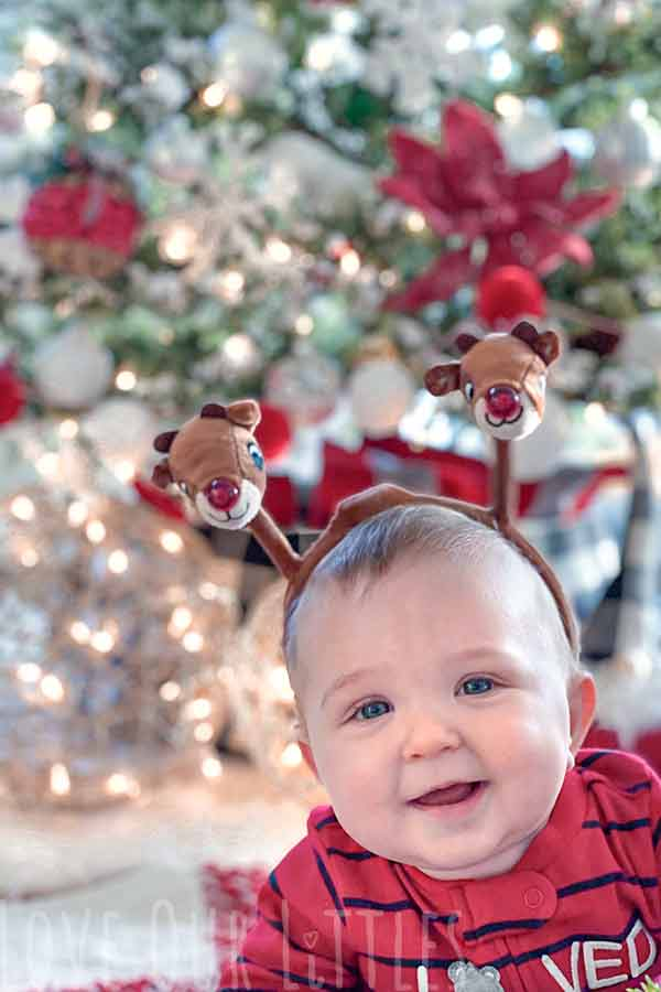 Christmas photo of baby on stomach in front of a lit Christmas tree.