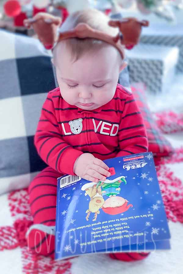 Baby sitting with a Christmas book for his first christmas photos.