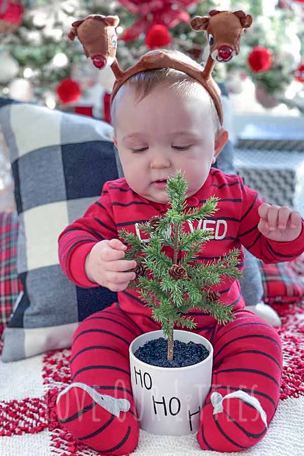 Christmas photo idea with baby sitting with a fake miniature christmas tree between his legs.