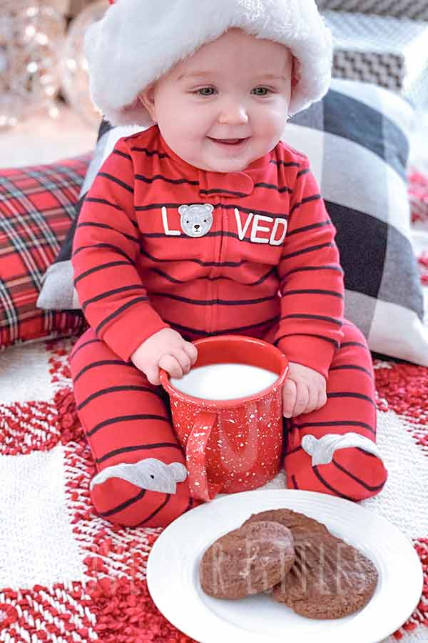 Baby boy wearing a Santa hat sitting with a mug of milk and cookies in a christmas photo.