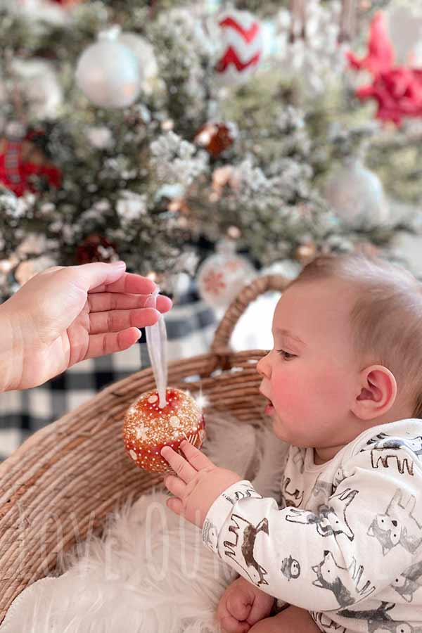 Baby in front of christmas tree looking at a sparkly ornament.