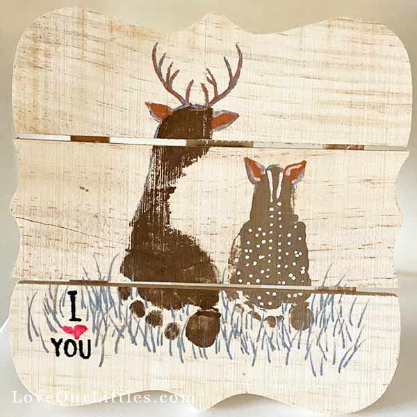 Baby and toddler footprints made into a buck and a fawn sitting in a field on a decorative wooden board.