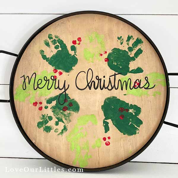 Handprint wreath stamped on a wooden round tray.