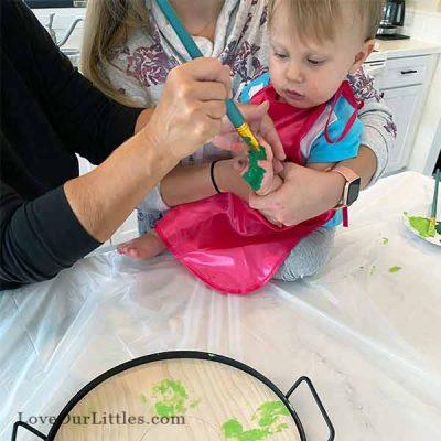 Toddler wearing pink smock doing handprint crafts.