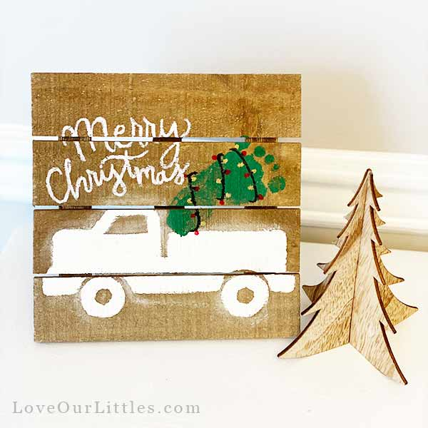 Footprint Christmas art with baby footprint of an old vintage truck with a Christmas tree footprint in the bed of the truck.