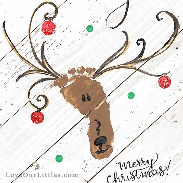 Baby footprint turned into a Christmas reindeer on a wooden plank for art.