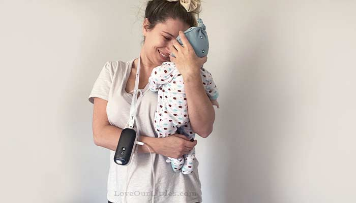 Woman holding her baby while pumping wearing the spectra handsfree caracups.