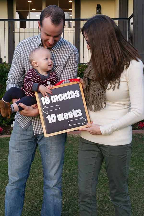Mom and dad holding a sign that shows the age of the toddler and how far along pregnant the mom is.
