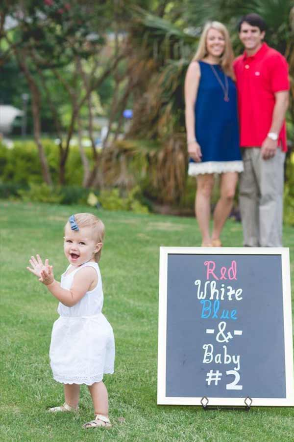 Little girl standing in foreground with parents in the background a big chalkboard sign announcing the second baby.