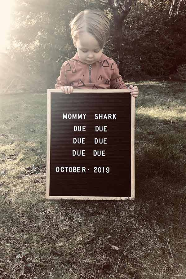 Toddler boy holding a letter board announcing pregnancy of second baby.