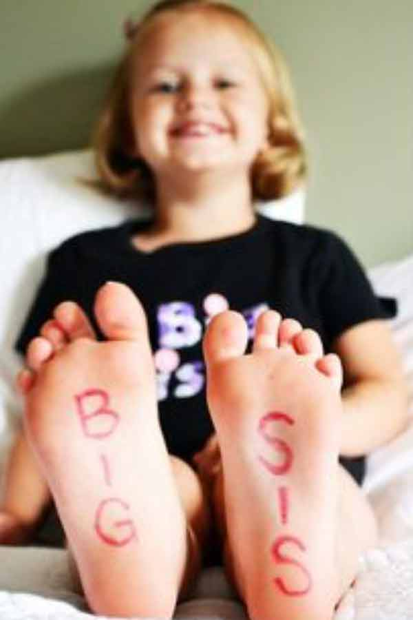 Little girl sitting on a bed with her feet in focus that say big sister.