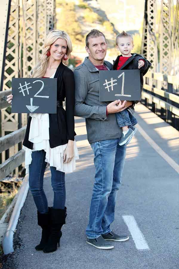 Mom dad and toddler on a bridge posing for second baby photo announcnemt holding signs with numbers.