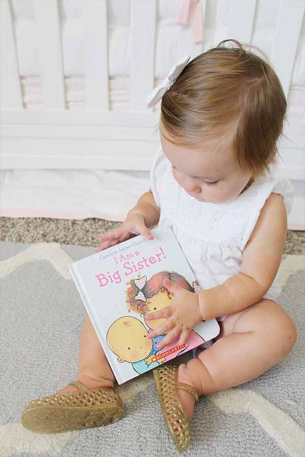 Toddler girl holding a big sister book for second baby announcement picture.