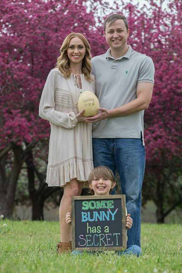 Little boy holding a pregnancy announcement sign with mom and dad in the background holding an egg.