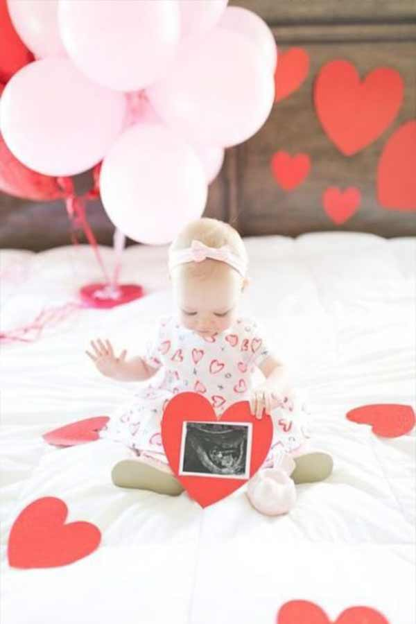Baby girl sitting on a bed with cut out hearts and balloons holding an ultrasound picture.