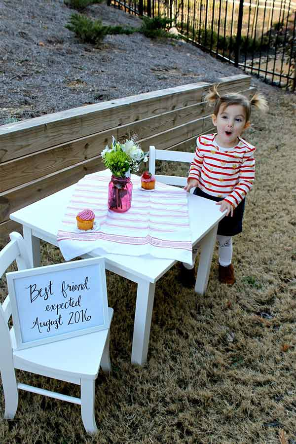 Little girl sitting at a white kid table doing a second baby announcement photo.