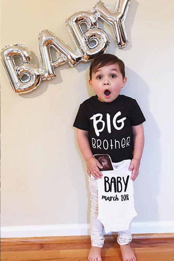 Little boy wearing a big brother shirt and holding a baby onesie with a big oh baby balloon behind him.