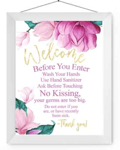 Pink and green floral welcome sign in a white hanging frame