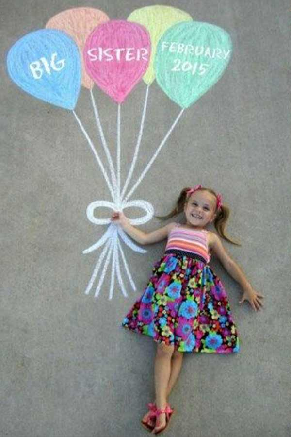Little girl lying on the cement ground pretending to hold onto balloons drawn with chalk.