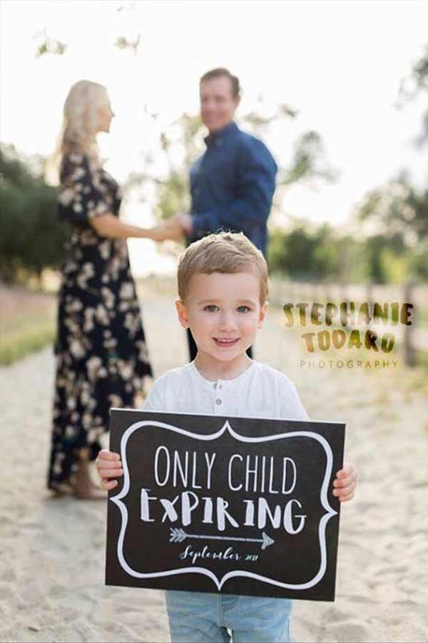 Little boy holding a chalkboard sign announcing the second baby pregnancy.