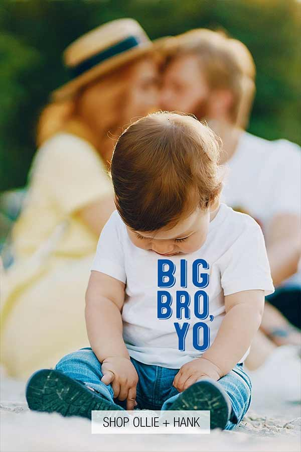 Toddler boy sitting in the foreground wearing a big brother t-shirt with parents kissing in the background/
