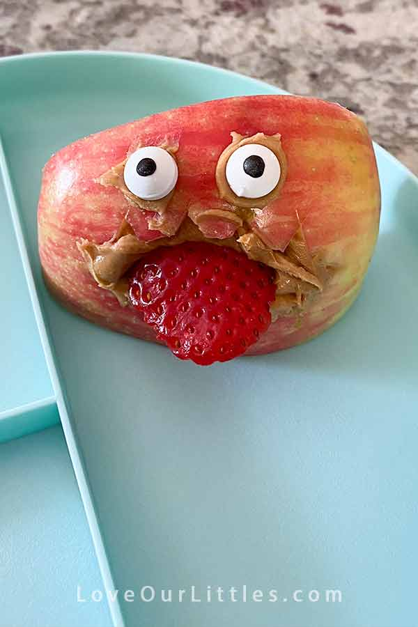 Apple slice made to look like a monster with it's tongue sticking out using a strawberry.