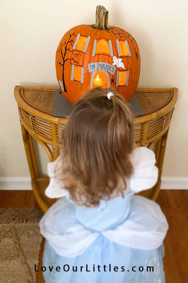 Little girl looking at a pumpkin.