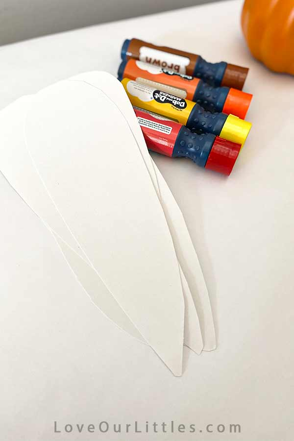 White paper cut into corn cob shapes and dot markers.