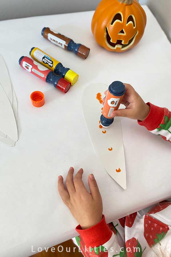 Toddler painting a fall craft with dot markers.