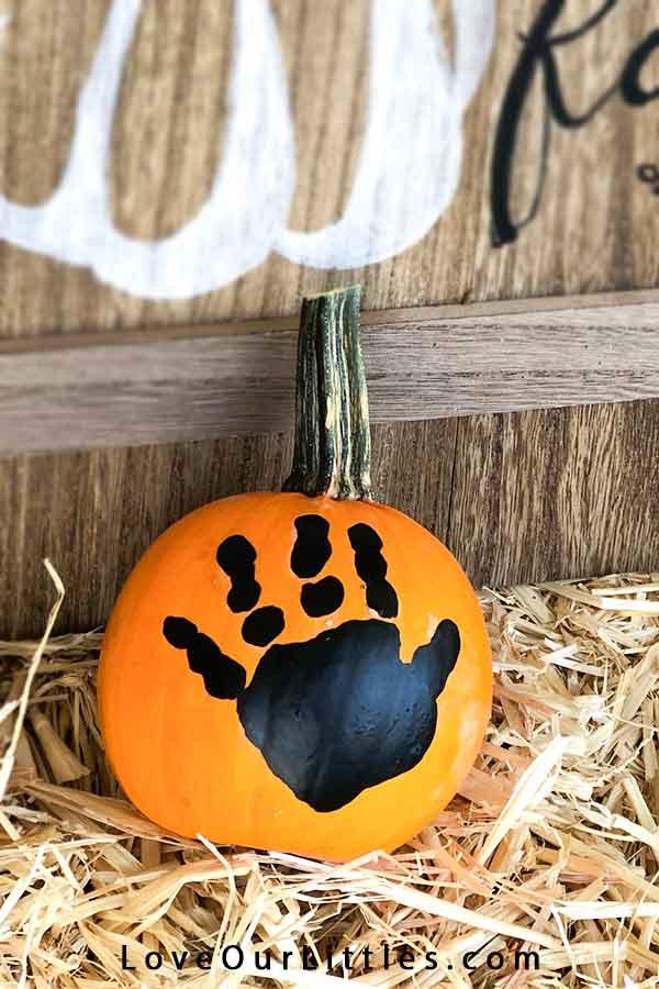 Pumpkin handprint craft on a real pumpkin.